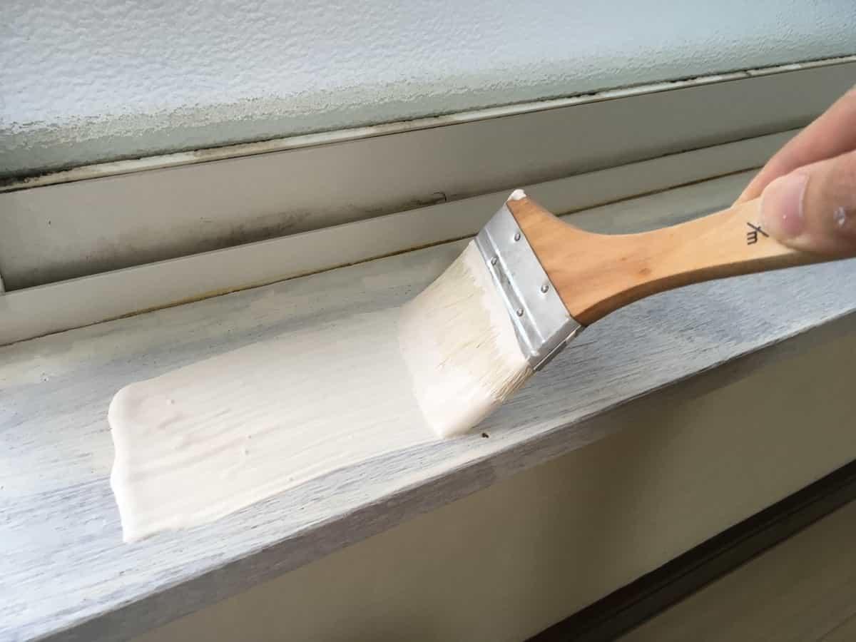 窓枠の木部を二度塗りする様子